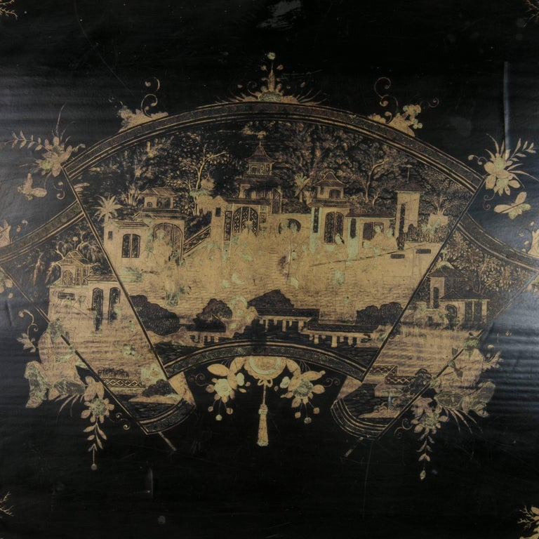 Found in France, this very large 19th century black lacquer wooden tray dates to the period of Napoleon III,  An ornately hand painted scene in gold chinoiserie features a grand procession in front of an imperial palace displayed on an unfurling