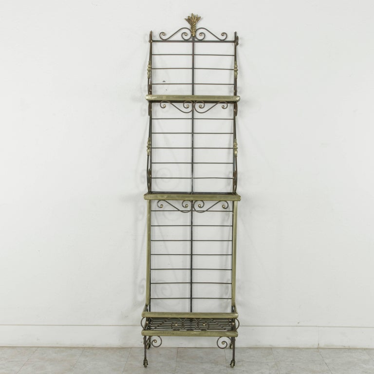 A rare find in a unique small scale, this French iron baker's rack from Normandy is trimmed in brass around each of its three shelves. The shelves are joined by scrolling iron detailed with brass turnings that lend support as well as an aesthetic