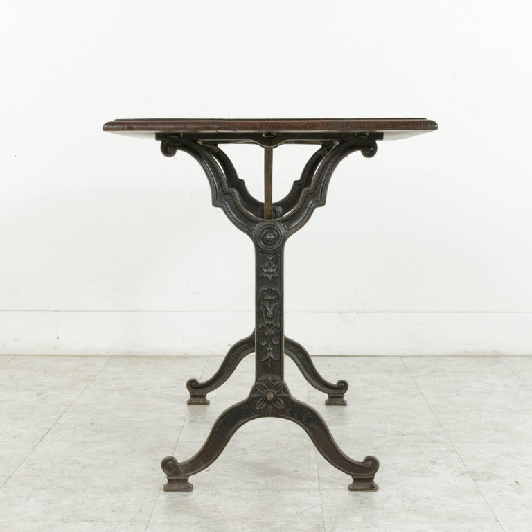 Originally used in a French brasserie around the turn of the 20th century, this Art Nouveau period bistro table or cafe table features a cast iron base and a beveled oak top constructed from three planks. The iron base of the piece is adorned with