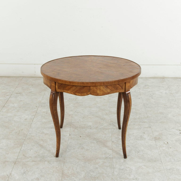 This early 20th century French walnut marquetry coffee table features a banded round top inlaid with a geometric sunburst pattern. Gently curved cabriole legs complete the look. Ideal as a coffee table or cocktail table for small scale living, circa