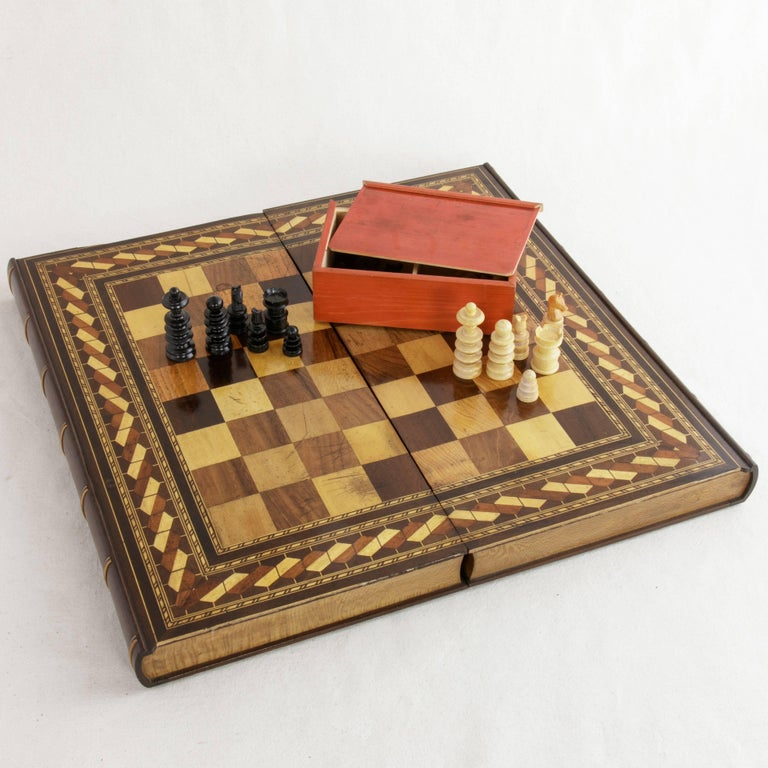 Taking the form of two stacked books, this hinged marquetry game box features a chess and checker board on the exterior and marquetry backgammon board on the interior. Displaying intricate inlay of exotic woods in geometric patterns, this box