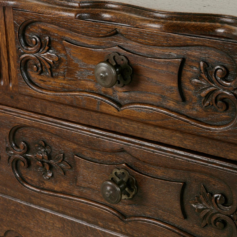 This early 20th century French Louis XV style oak commode sauteuse or chest features hand carved details of leaves, flowers and scrolling and is finished with a beveled oak top made from a single plank of wood. A commode sauteuse or