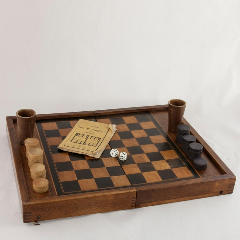 This French walnut marquetry folding game box from the turn of the twentieth century is for both checkers and backgammon. It is finely constructed with dovetailed corners, inset hinges, and a locking brass hook on each side. The checker board side
