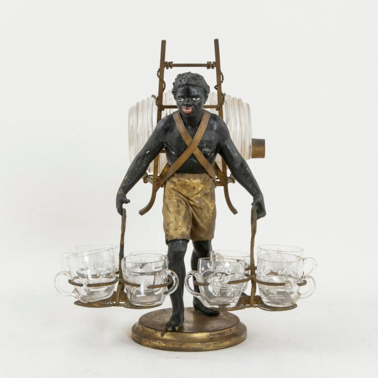 This mid-nineteenth century French Napoleon III period liqueur caddy or cave a liqueurs features a Blackamoor figure wearing gold breeches resting on a circular brass base. He carries a glass barrel on his back and two baskets in his hands, each