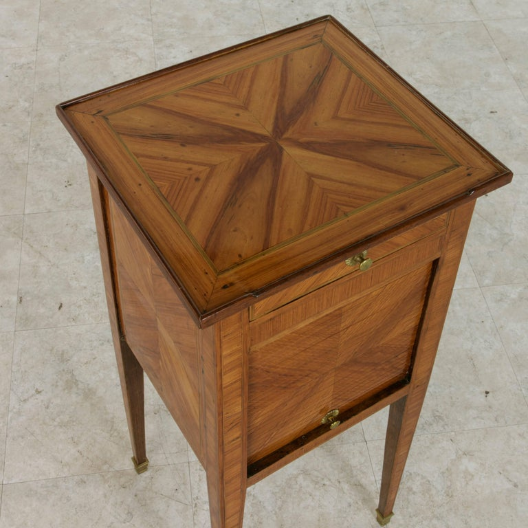 This eighteenth century Louis XVI period side table or nightstand is finished on all sides with exquisite book-matched rosewood marquetry detailed with fine lines of inlaid sycamore that frame the top and sides. Bronze sabots finish the tapered