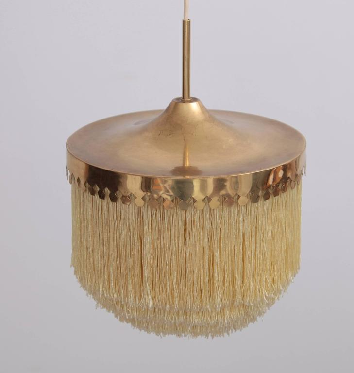 Pendant light with cut brass canopy and ivory-colored silk fringes. Good condition with signs of wear in line with age to both the brass and the silk.
