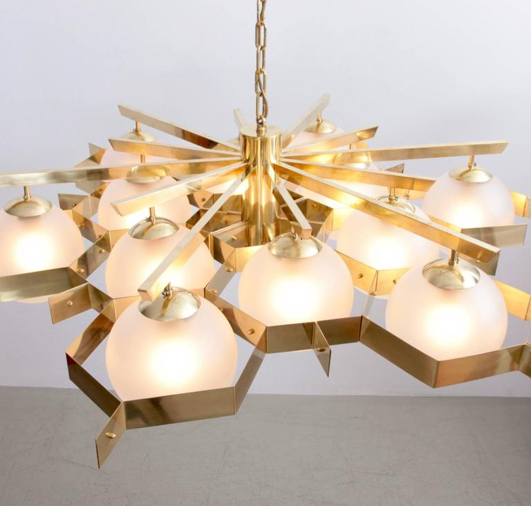 Very huge brass structure and glass chandelier. The impressive piece is in excellent condition. 12 x E27 / model A Bulb.