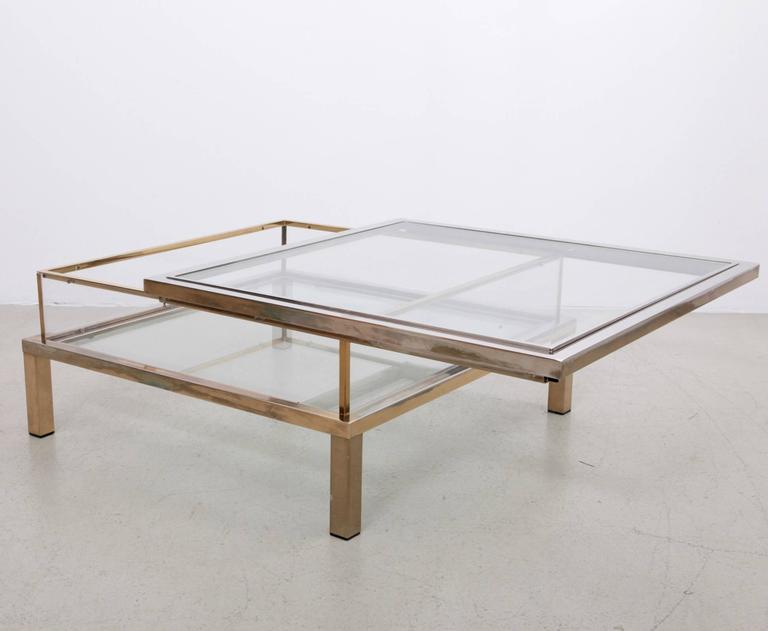 Large square glass table with sliding top by Maison Jansen. Frame has an total original gold-plated and chrome metal finish. The table shows a nice patina.