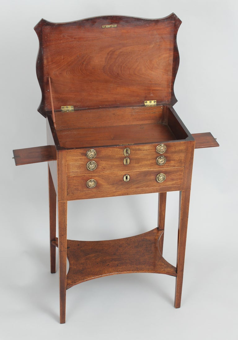George III period mahogany worktable; the overhanging serpentine hinged top with a kingwood cross-banded border, enclosing a compartment behind two dummy-drawers, above a drawer with six adjustable dividers; the sides fitted with two small slides