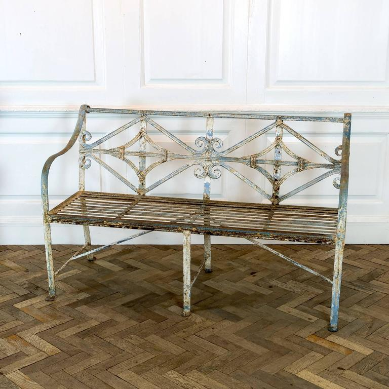 With faded blue and white paint work, floral detail and slatted seat rest.