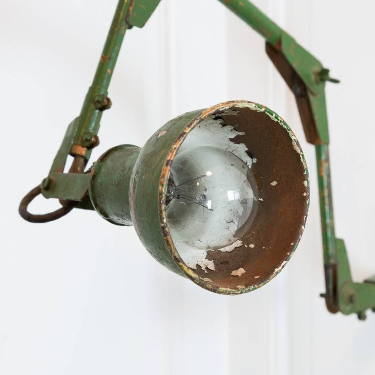 Adjustable wall-mounted angle poise with distressed green paint, possibly by The Dugdill Company, circa 1930s.