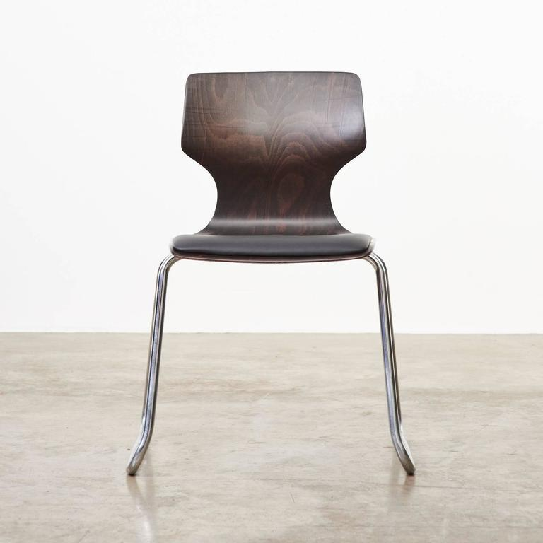 A Mid-Century West German stackable dining chair produced by the Flötotto company in the 1950s. The black Italian leather reupholstered cushion on ply 'pagwood' seat above the tubular chrome base frame. Multiples available.