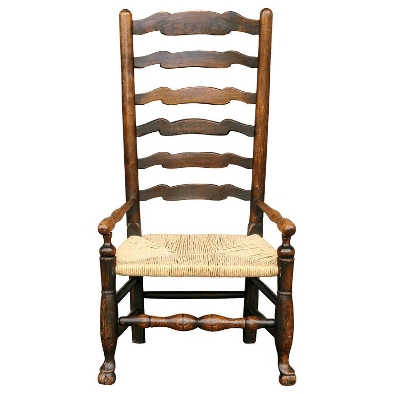 Late 18th century country ladder back armchair from ash wood. Typical of chairs attributed to the Lancashire parish of Wigan, this chair features turned uprights, with domed and nipple finials, connected by wavy line slats and boldly turned