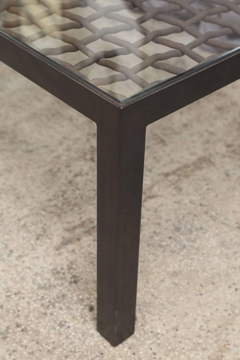 Custom coffee table with 19th century basket-weave iron element inset into a new steel base, under a glass top.