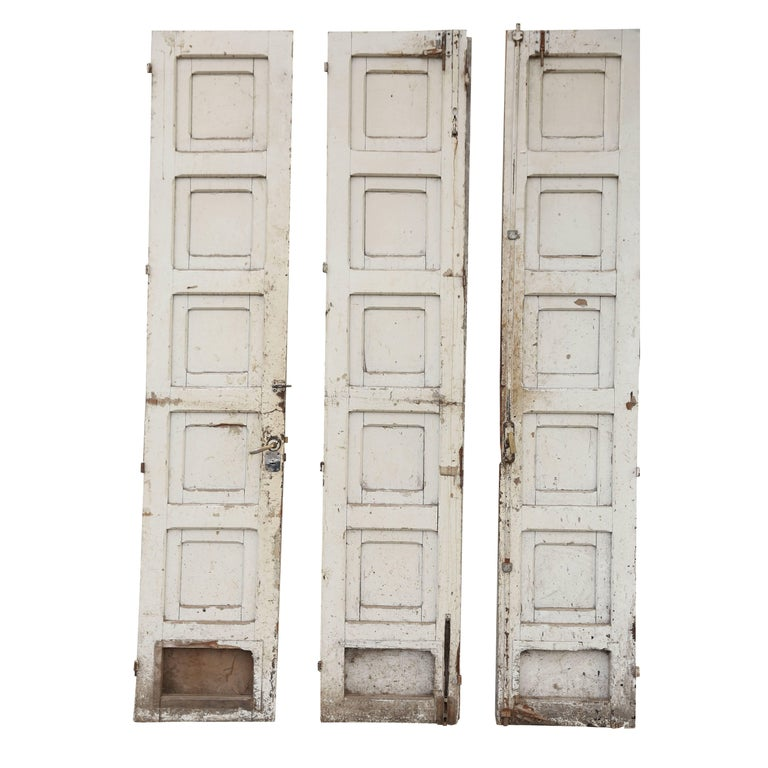 Three antique French doors: heavy painted antique wooden doors (circa 1910-1930, France), deeply carved with geometrical moldings, in their original paint. Two doors hinge together and attach to the right side of the doorway and the third door