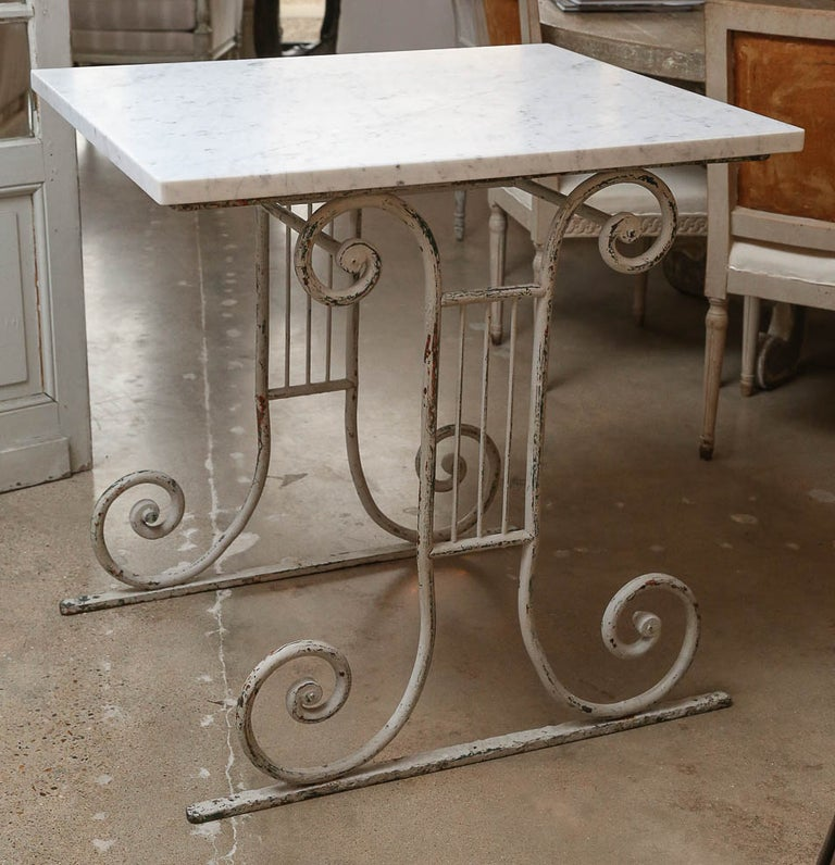 Marble-top white painted base table, table de Boucherie (French butcher's table), dating to the late 19th century. Later Carrara marble top raised upon a painted scrolled iron base.
