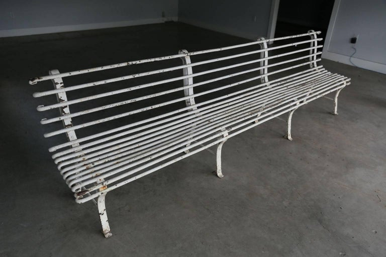Long French iron bench in early white paint. Excellent example of early 20th century quality French cast and wrought iron. In stabile, sturdy good condition and a nice heavy weight. Ready to be installed in your garden or outdoor space.
