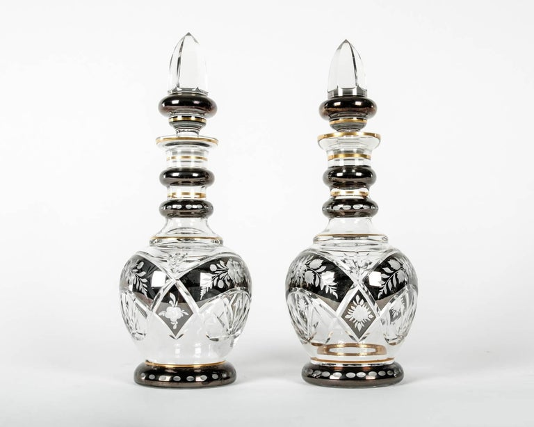 Vintage pair of cut crystal with etched design details and arched band cut and gold trim barware drinks decanter set. Each decanter is in excellent vintage condition. Each decanter measures about 13.5 inches diameter x 5.5 diameter.