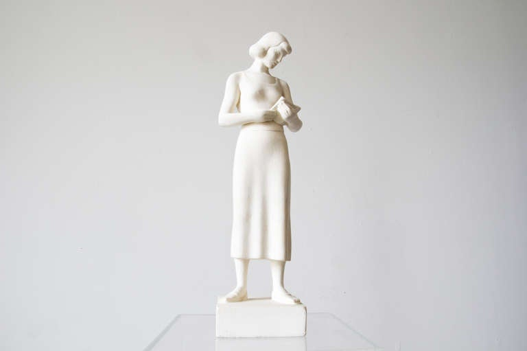 A plaster sculpture signed by Maurice Glickman of a woman reading a book. Made under the Work Progress Administration, a program under the FDR New Deal to promote artistry throughout the United States.