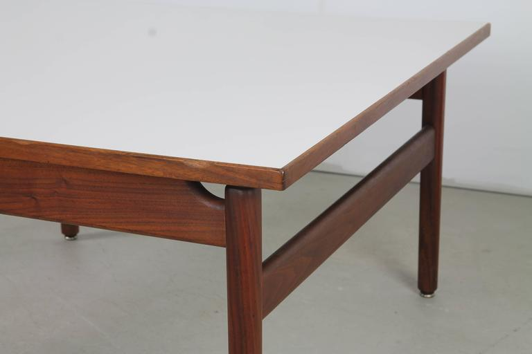 Versatile square coffee or cocktail table by Jens Risom, with straight, turned walnut legs, squared stretchers and a floating white laminate top.