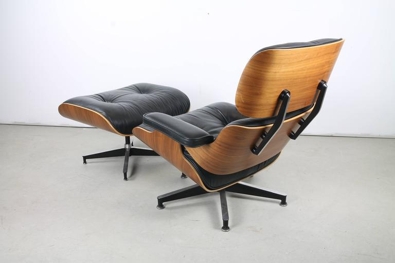 An immaculate 670 lounge and 671 ottoman in walnut by Charles and Ray Eames for Herman Miller, featuring sinuous multi-bend plywood shells framing supple, tufted leather upholstery. The chair swivels on a chromed steel 5-point base. The ottoman is