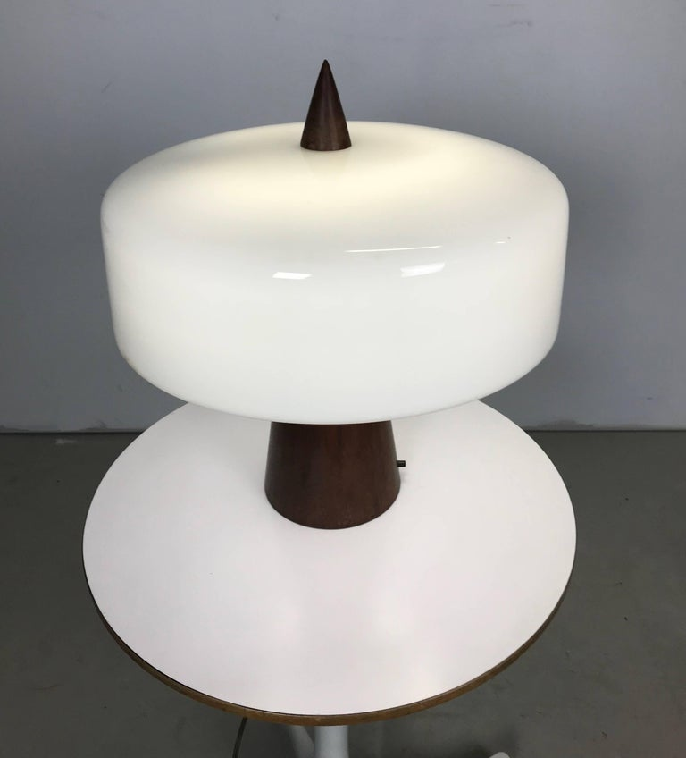 This is a one of a kind turned walnut and milk glass desk lamp. It was designed, circa 1960 by Phillip Enfield for a friend and client. It is in excellent original condition and has been owned by the same person since new. A fine and rare piece of
