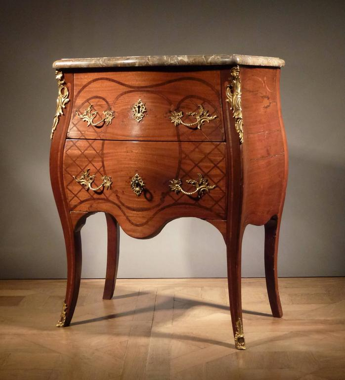 Veneered with mahogany and amaranth. The grey-white-rose marble top above two drawers