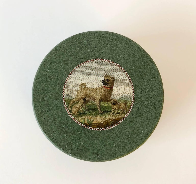A green hardstone circular box with detachable cover set with a micromosaic depicting a mother dog nursing a puppy and protecting another puppy with her paw. 