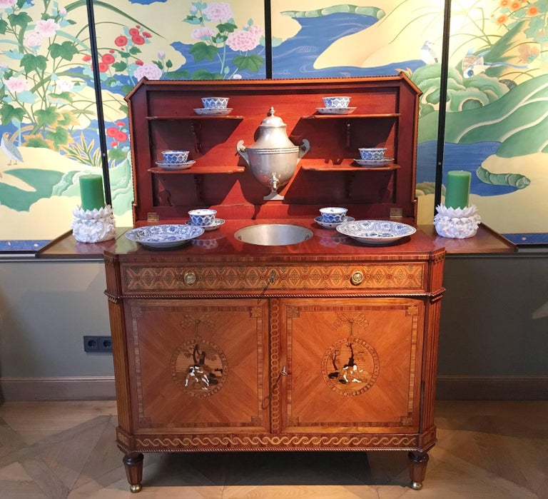 Veneered with kingwood, satinwood, fruitwood  the hinged top centered by an oval panel with an allegorical trophy, opening to a pewter basin and fountain with folding shelves on each side, above a long frieze drawer divided into two compartments and