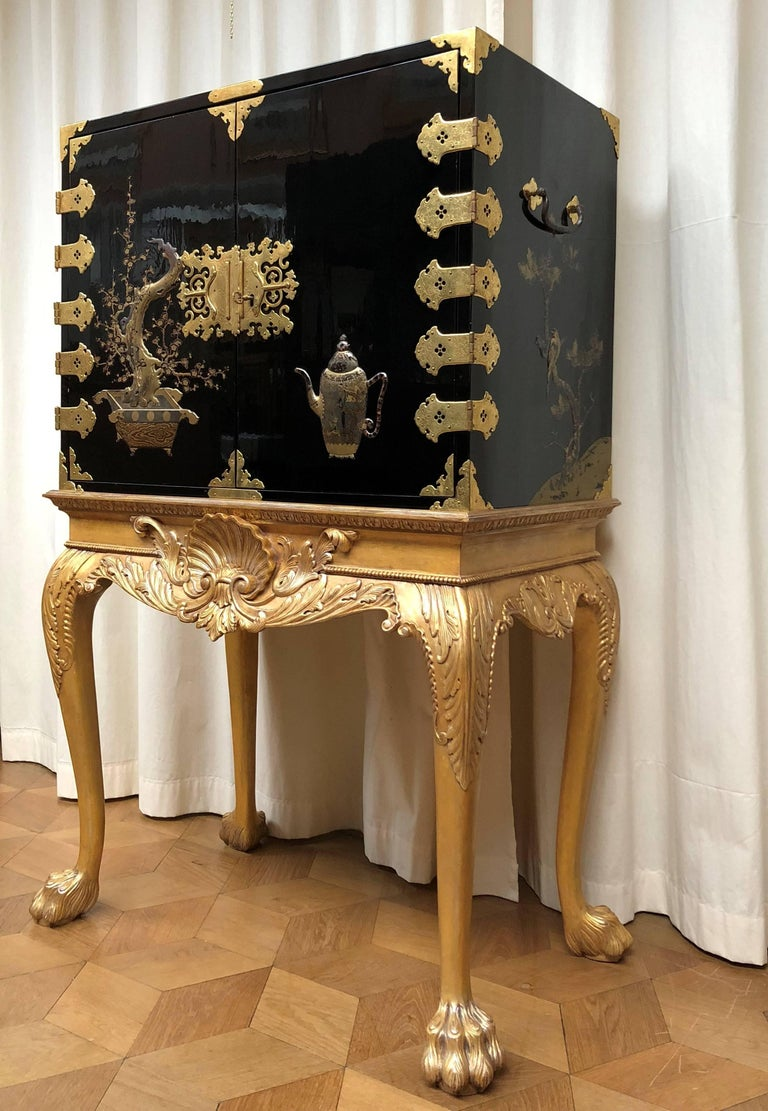 This rectangular lacquer cabinet is executed in black and gold reliëf lacquer. The hinged doors decorated with a teapot and a bonsai tree, opening to an interior fitted with ten drawers decorated with landscapes, the sides each with two birds on a