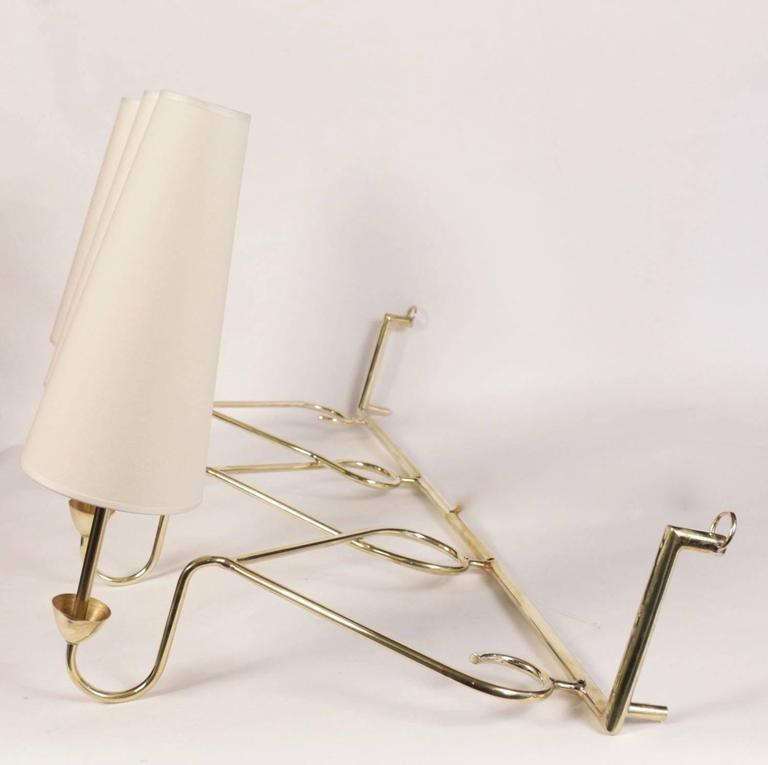 Large 1950s sconce attributed to House Stilnovo.  Nice curved brass work. Each sconce's base underlined with a brass cup. Three lighted arms surmounted by custom lampshades.