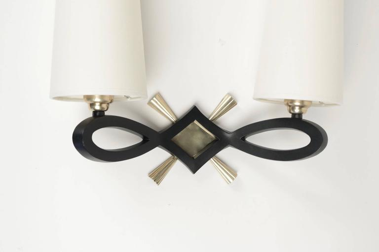 1940 pair of wall lights by Marcel Guillemard.  Each sconce consists in a large black lacquered bronze knot highlighted with a gilded bronze diamond-shaped plate and cross.  Two lighted arms and two white ivory cotton lampshades.  The signature is