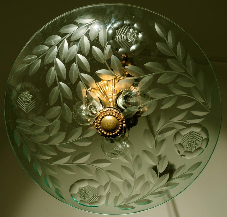 A big discs in Nile green crystal etched acid supported by a rod frame. Precious engravings on the disc.