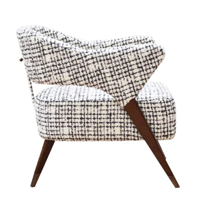 Large lounge armchair designed by Monica Ballesio. Inspired from the fifties, this armchair was created to complete a series of authentic pieces of furniture from that period.  The curved back and arms are made in one piece connected to the legs.