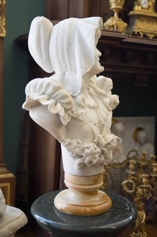 A charming late 19th century Italian Carrara marble bust of a smiling young woman. The finely carved bust depicts a young woman wearing a large hat and a stem with 2 cherries in her mouth.  Circa 1890