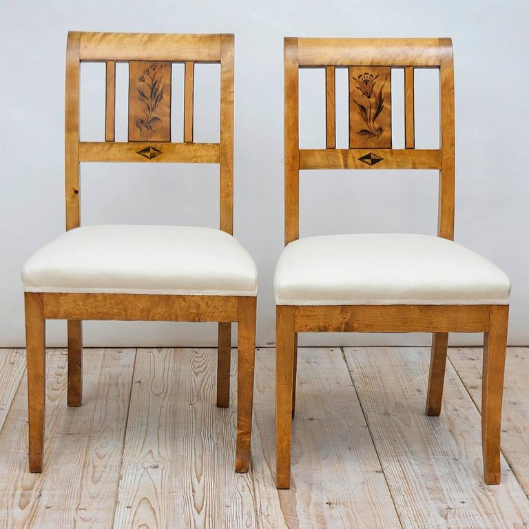 A pair of comfortable Swedish Art Deco side chairs in birch with black stenciled flowers on back-splat, square saber front and back legs and upholstered seat. Signed C. J. Svensson, Goteborg, 1925.
