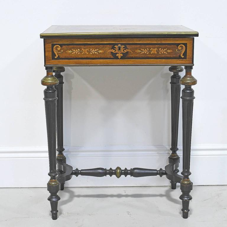 "From the reign of Napoleon III, a parcel-ebonized vanity table decorated with intricate marquetry inlays on all four sides of apron and top, turned and fluted ebonized legs with brass fittings, and ""H"" stretcher. Opens to reveal divided"