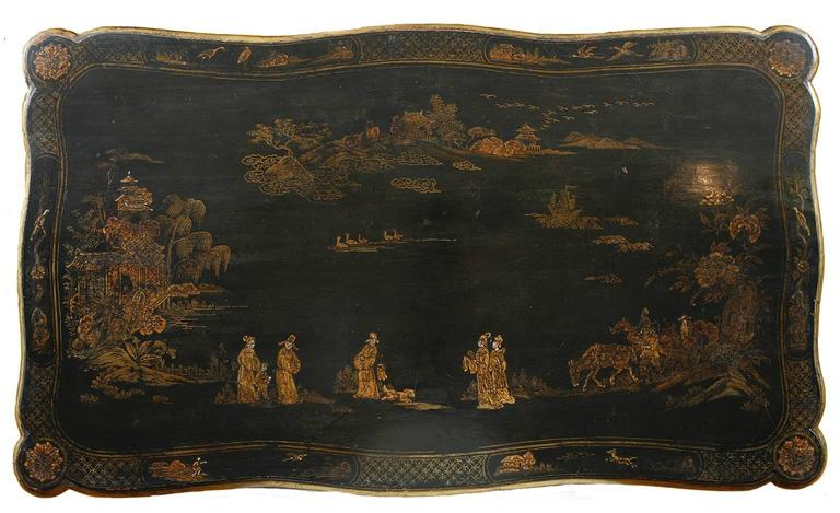 A very lovely chinoiserie table in black lacquer with decorations in gold paint of scenes from Chinese village life that include: Men astride horses holding nets with dogs afoot, women strolling along a path with pagodas and houses in the distance