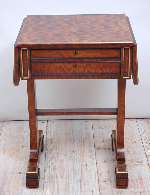 A fine English Regency work or side table on trestle base with drop leaves in beautiful plum mahogany with brass banding on edge of table and ebonized banding around drawers and block feet. Back and front of table are identical with front offering