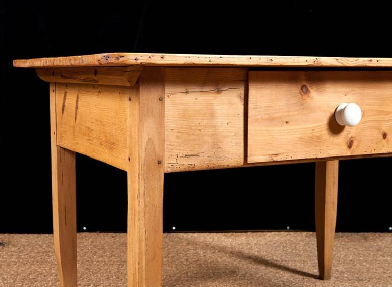 A rectangular pine table with mortise joint, pegged construction and offering one large storage drawer, Northern Germany, circa early 1800s.  Perfect as a kitchen work table Note: Should it be needed, we can adapt this to a coffee table and/or paint