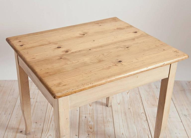 North German Biedermeier style work table in pine. Perfect as a writing table, a lamp table, nightstand or even as an work table in the kitchen. Could also be reduced to coffee table height. Legs are finished with a chalk wash and top with oil and
