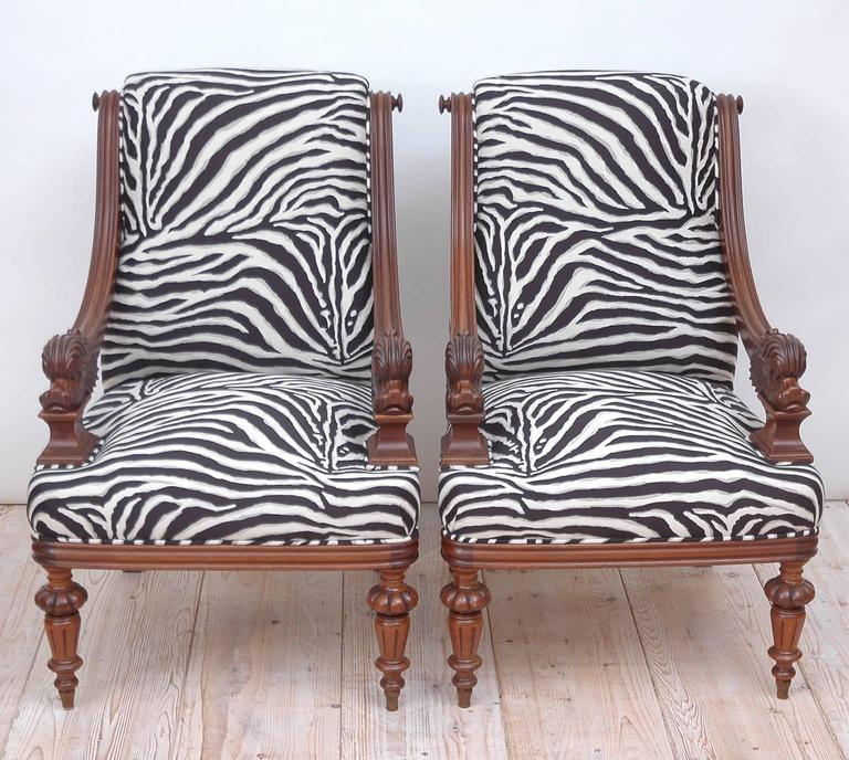 A pair of Napoleon III bergères in walnut with carved dolphins as armrests, turned and carved legs. Newly upholstered in Robert Allen cotton