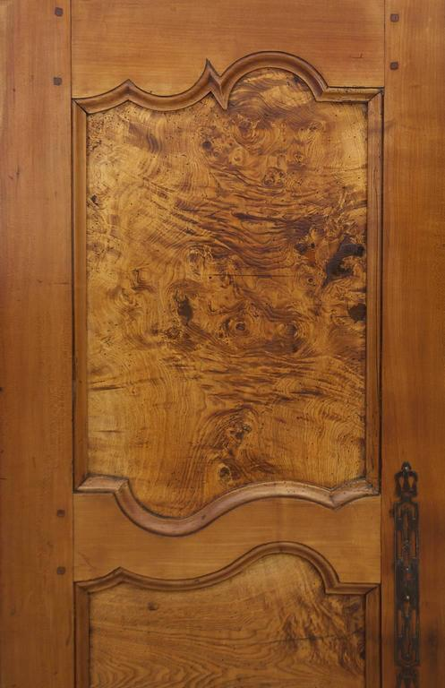 A French Armoire from Brittany in Walnut, Cherry and Oak, and Olive Ash Burl panels with mortise and peg construction, original lock, hardware and hinges, circa 1840.  Offers the potencial of ample storage for clothing, linens or as a cupboard or