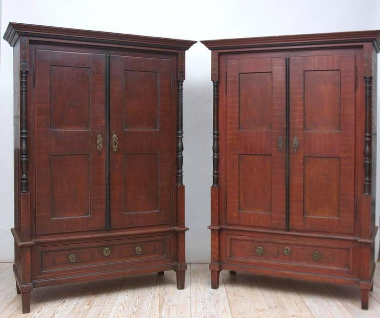 From the Austro-Hungarian Empire, a nearly identical pair of armoires with ebonized columns and astragal, and the original tooled and grained finish. Offers divided storage with adjustable shelving, primitive hanging rod in one and a small original