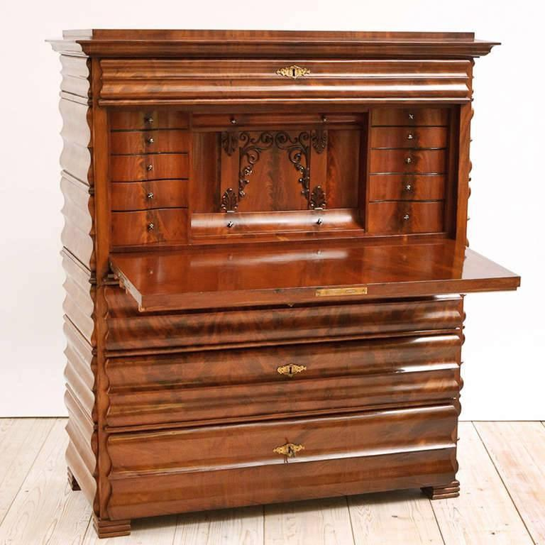 A captivating one of a kind Louis Phillip secretary in book-matched, flame mahogany with shaped, curvi-linear drawer fronts and faux drawer fronts on the fall-front and the sides. Offers four hidden compartments for valuables. Northern Germany,