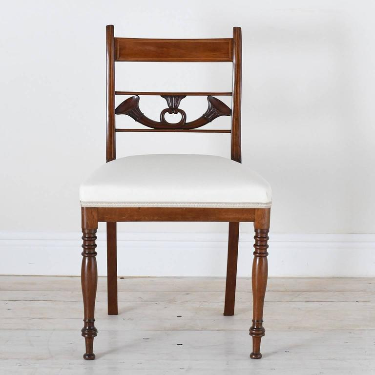 A fine set of four English Regency dining chairs in mahogany with carved bugles resting on back chair rail below the top slat which is line inlaid, with turned front legs and saber rear legs, and upholstered seat, England, circa 1830. Measures: 19