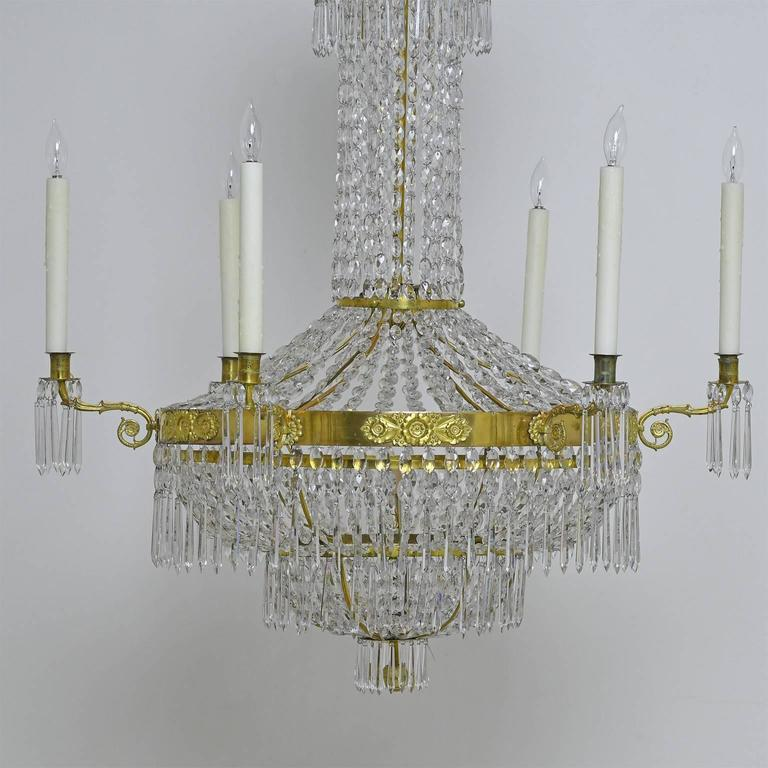 A fine 18th century or early 19th century Antique Gustavian or Swedish Empire crystal chandelier with brass armature featuring a center ring with thinly pressed rosettes and foliage on brass appliqué between the six candle holders.  The diminishing