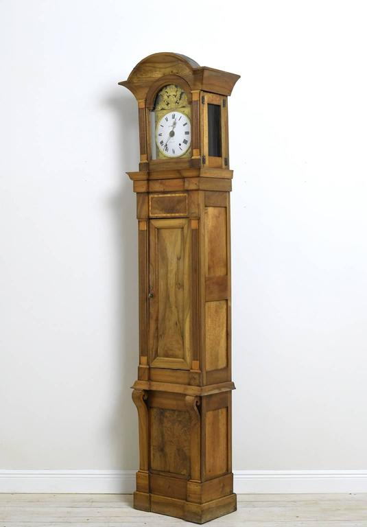 "From the historically important city of Lyon, an impressive and well-proportioned eighteenth century Louis XVI long case clock in walnut with inlays. Arched bonnet over arched glass-paneled door opens to an enamel dial, reading ""Martin a Lyon"","