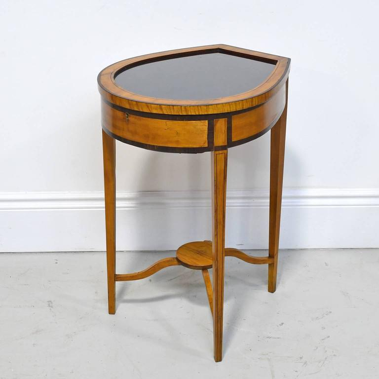 A pair of Edwardian satinwood vitrine tables with shaped tops with banded edges above single drawer, and raised on square tapering legs with string inlay, joined by stretchers surmounted by circular shelf. Tables have glass tops with deep wells to