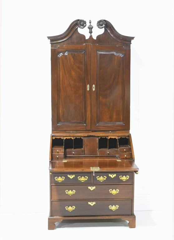 A fine 18th century George III English bureau bookcase secretary in solid West Indies/ Cuban mahogany. The bonnet features a swan neck, broken-scroll pediment with carved rosettes and a center finial. Upper solid door panels are raised and interior